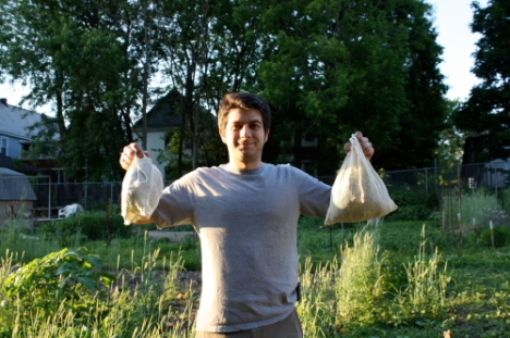 K holding bags of lettuce and spinach from our garden